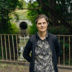 portret kobiety stojącej na tle zielonych drzew i małej rzeki