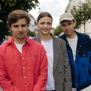 Stojąc na ulicy w obiektyw patrzy trójka młodych, uśmiechniętych ludzi: mężczyzna w czerwonej koszuli i brązowych włosach, kobieta w marynarce w krateczkę i w gładko związanych włosach oraz mężczyzna w piaskowej czapce z daszkiem i granatowo-niebieskiej kurtce; w tle ciąg kamienic
