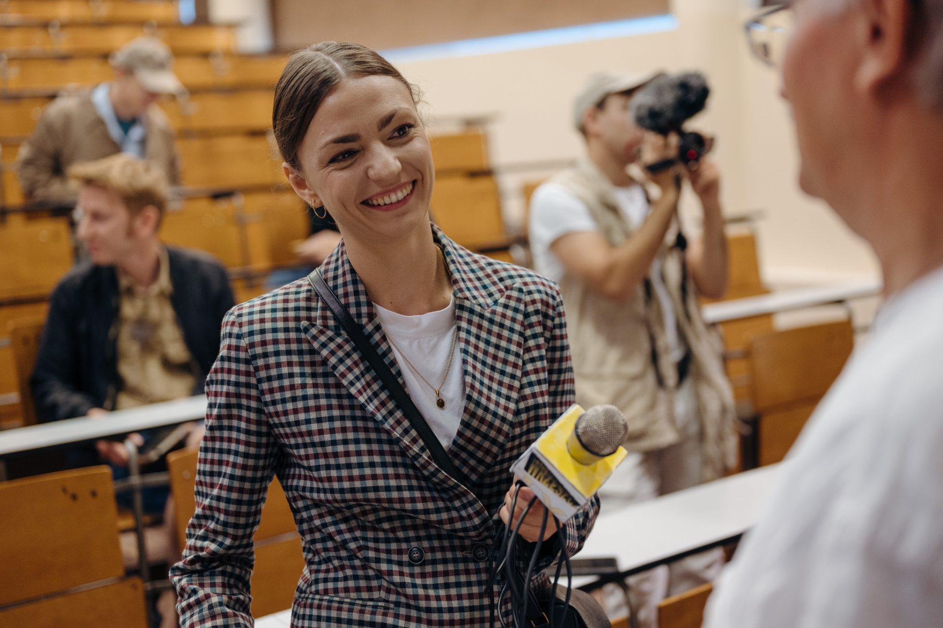 Aula uniwersytecka, w tle drewniane siedenia i kilkoro ludzi, na pierwszym plane młoda uśmiechnięta kobieta trzyma mikrofon przez ubranym na biało mężczyzną