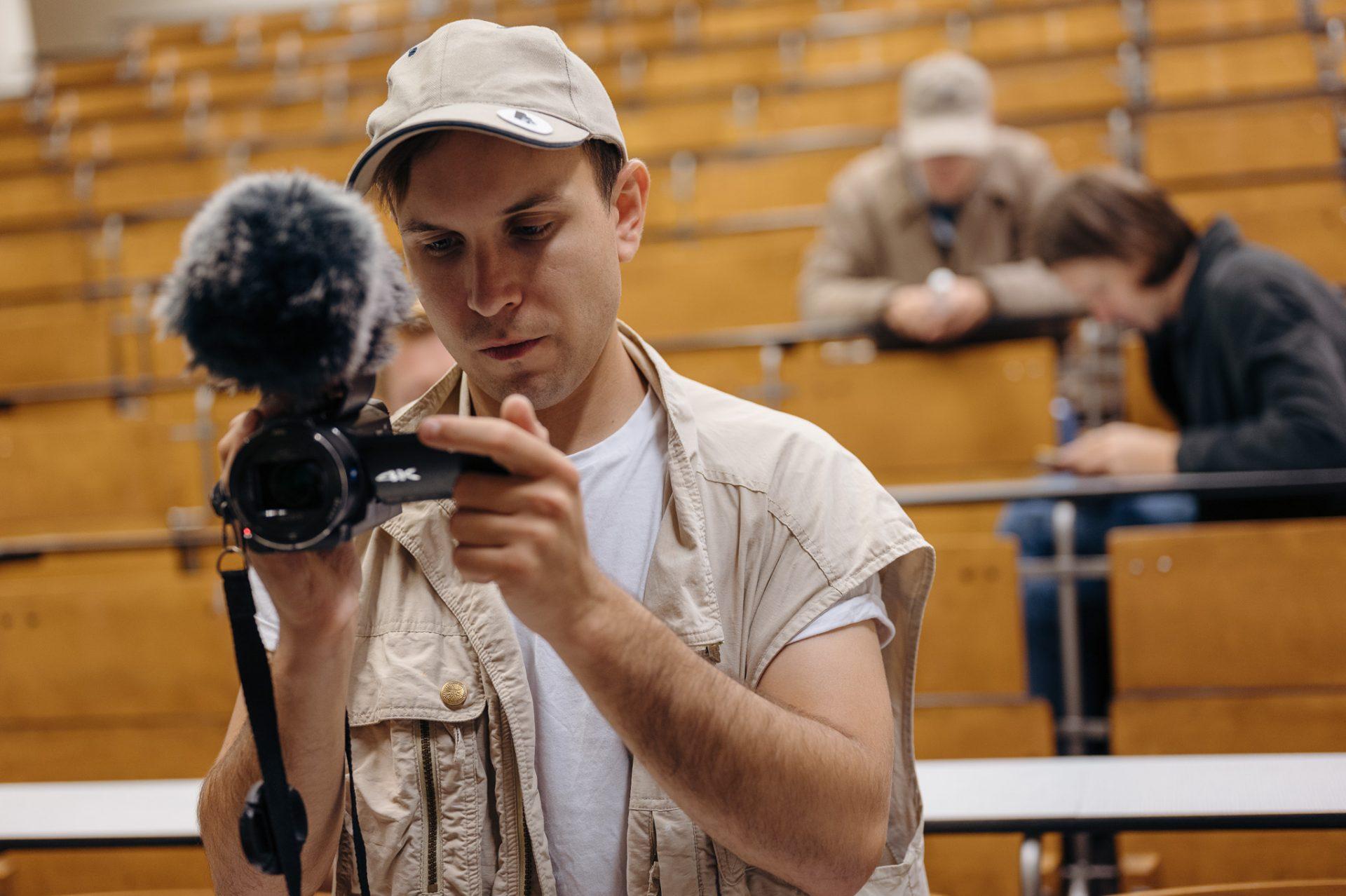 Aula uniwersytecka, w tle drewniane siedenia, na pierwszym planie młody mężczyzna nagrywa coś na kamerę