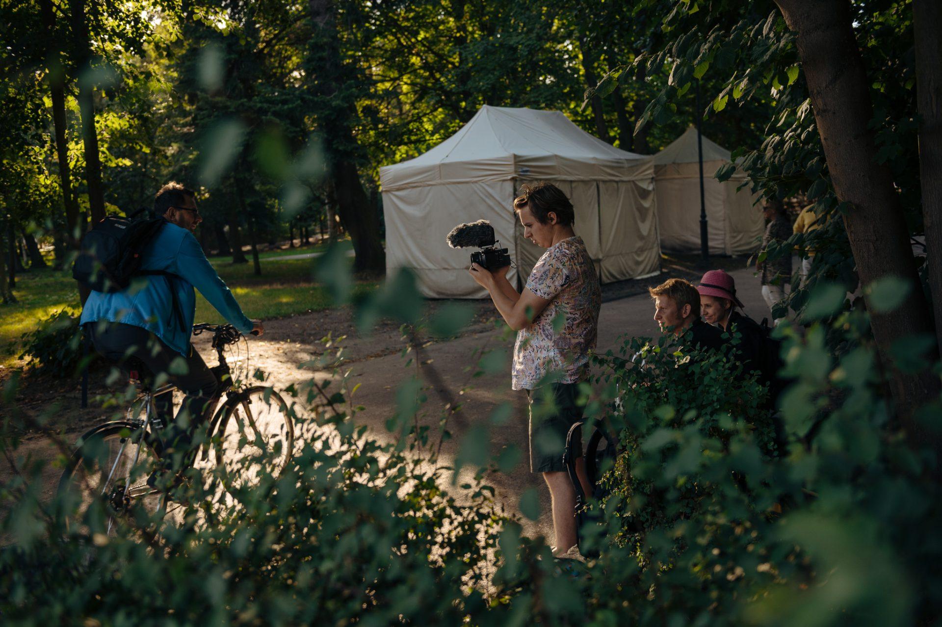 Park miejski latem, w głównym planie młody mężczyzna nagrywa coś w skupieniu na kamerę