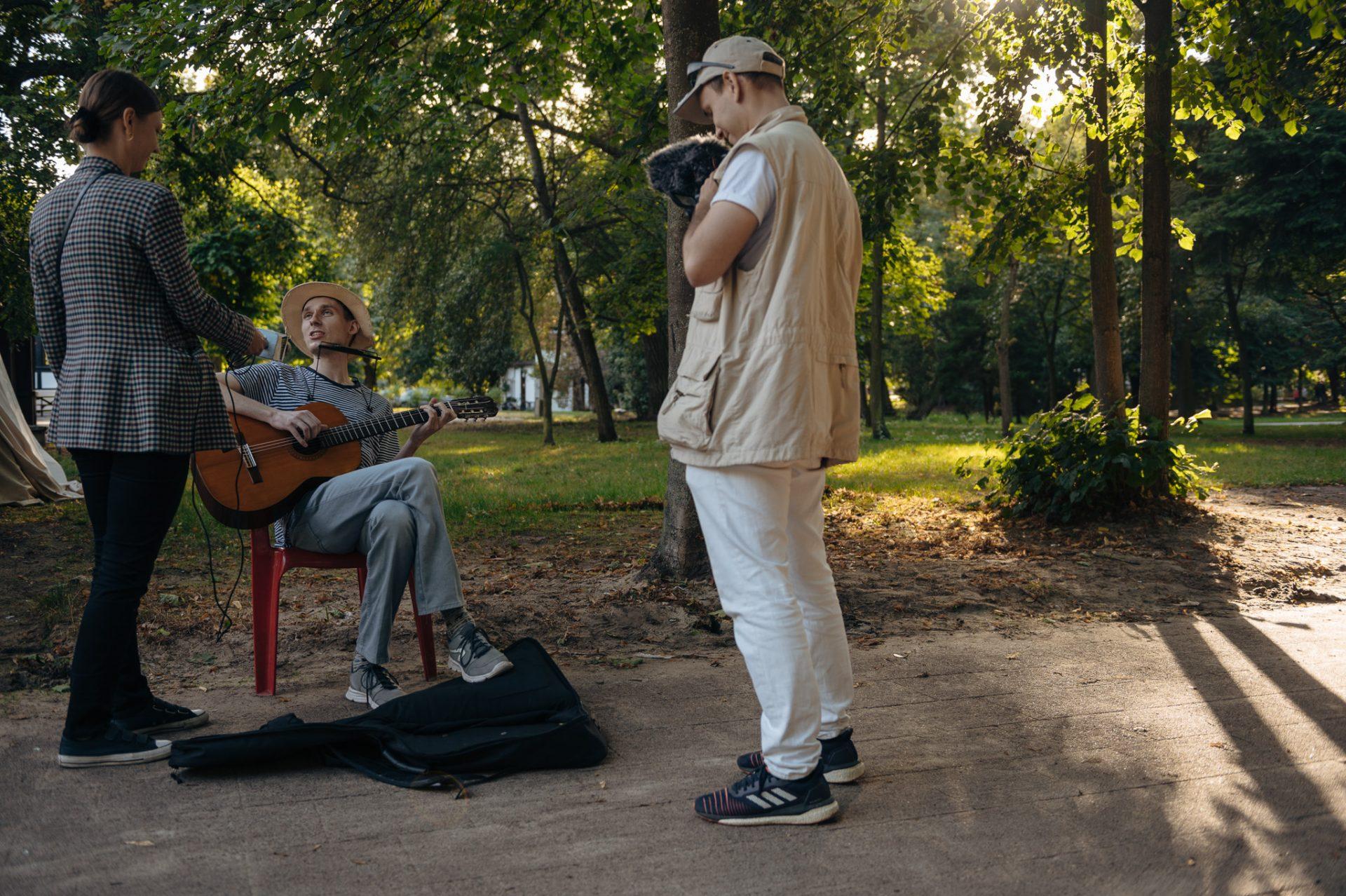 Troje młodych ludzi w zielonym parku: mężczyzna z kamerą, kobieta z mikrofonem rozmawiają z mężczyzną trzymającym w rękach gitarę