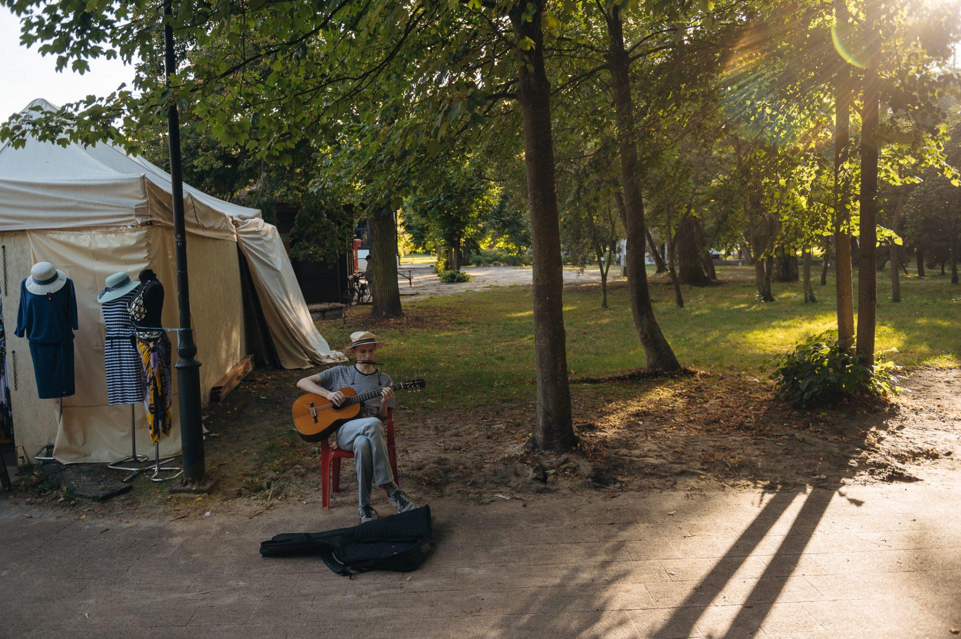 Młody mężczyzna w letnim kapeluszu siedzi na krześle w słonecznym parku i gra na gitarze oraz harmonijce, zbierając pieniądze do leżącego przed nim futerału gitary
