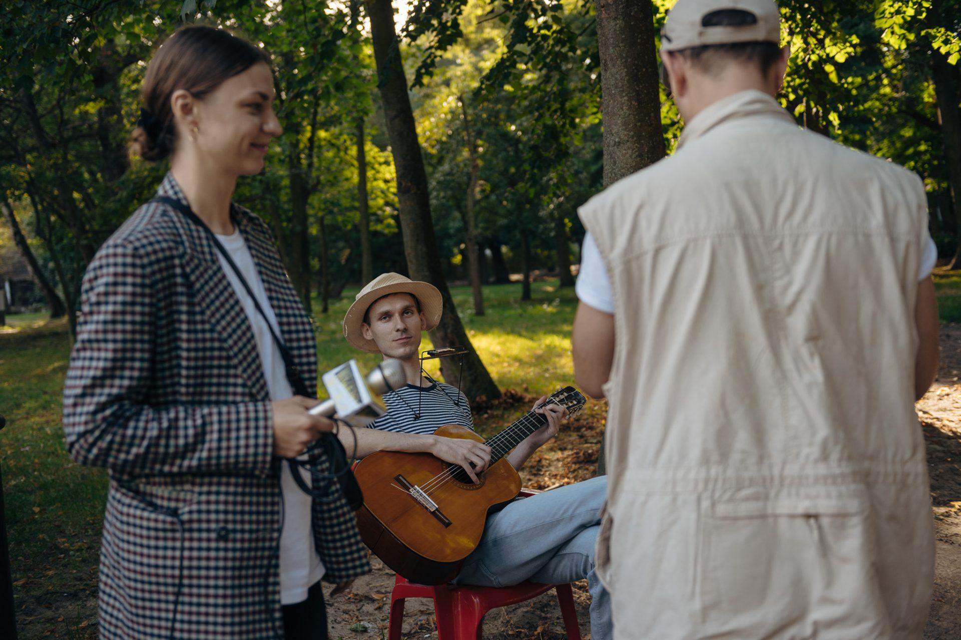 Trzy postacie w zielonym parku, na pierwszym planie młoda uśmiechnięta kobieta z mikrofonem w ręce oraz mężczyzna w piaskowej katanie stojący tyłem do obiektywu; głębiej siedzi młody mężczyzna w słomkowym kapeluszu, z gitarą i harmonijką ustną