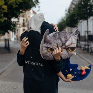 Na brukowanej ulicy tyłem do obiektywu przytulają się dwie ubrane w ciemne kolory osoby w kapturach nasuniętych na głowy; w rękach trzymają poduszki: jedna z pyszczkiem szarego kota, druga w kształcie księżyca