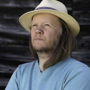 portret długowłosego, patrzącego w niebo mężczyzny w słomkowym kapeluszu