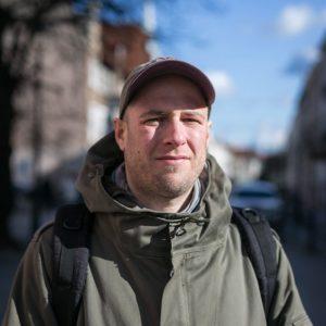 Stojąc na ulicy w obiektyw patrzy mężczyzna w kurtce kolory khaki, czapeczce z daszkiem i czarnym plecakiem, mruży oczy przed słońcem; w tle ciąg kamienic i błękitne niebo