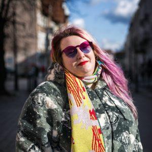 Stojąc na ulicy w obiektyw patrzy uśmiechnięta kobieta w długich kolorowych włosach, w kolorowych okularach przeciwsłonecznych, ubrana w sztuczne futerko z nadrukiem w niedźwiedzie polarne; w tle ciąg kamienic i błękitne niebo