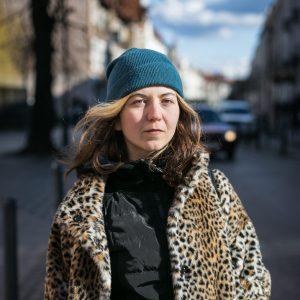 Stojąc na ulicy w obiektyw patrzy młoda kobieta w turkusowej czapce spod której wylewają się rozpuszczone włosy; ubrana jest w czarną kamizelę i sztuczne futerko ze zwierzęcym nadrukiem; w tle ciąg kamienic i błękitne niebo