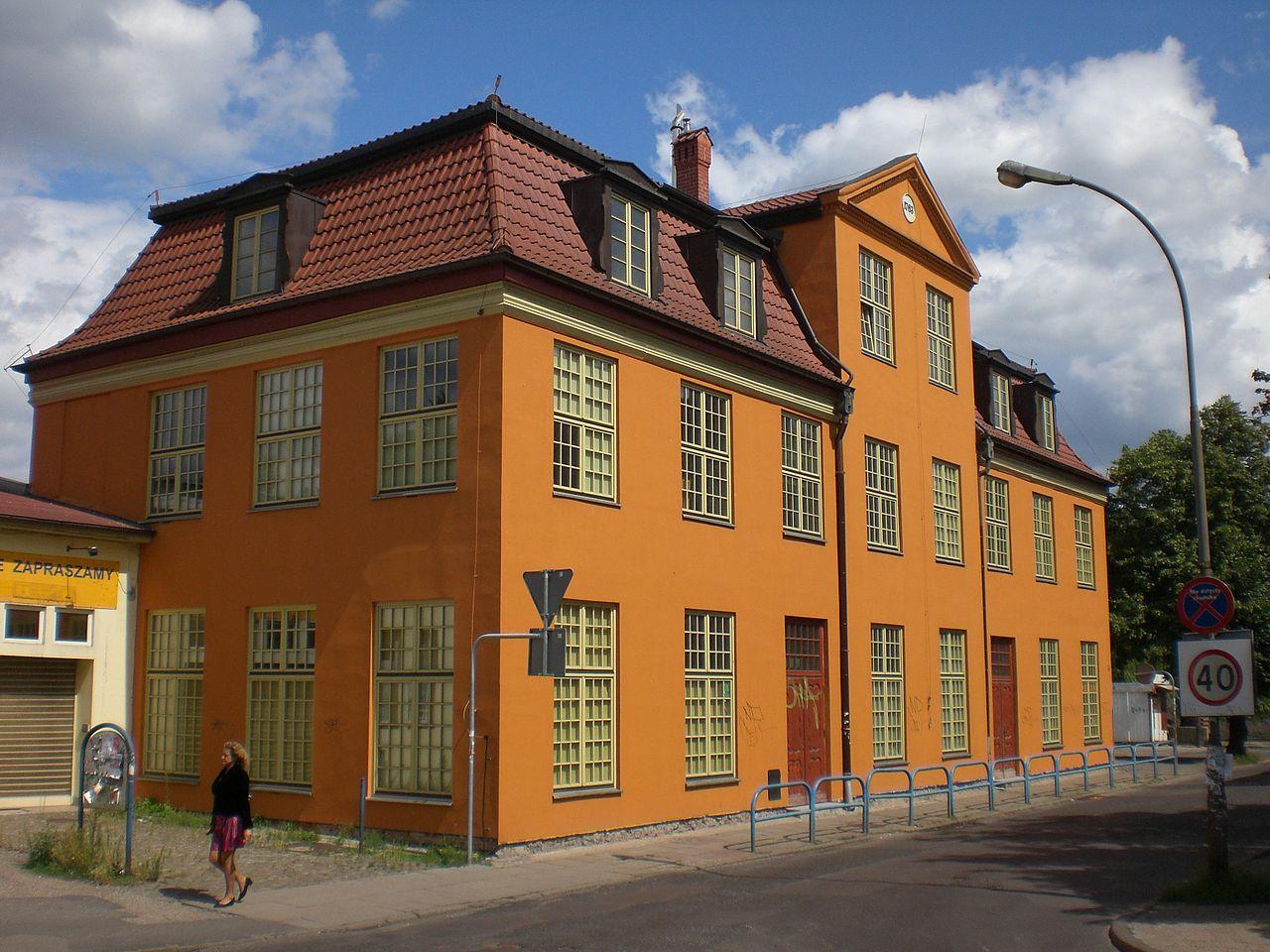 Piętrowy, zabytkowy budynek mieszkalny o pomarańczowej fasadzie i spadzistym dachu